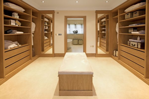 a large and luxurious walk-in wardrobe situated between the main bedroom and bathroom in an expensive new home.  Furnished and decorated by a leading Interior Designer whilst preparing this house as a show-home.